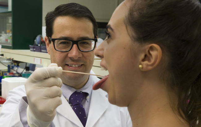 Dr. Walter Siqueira swabs a sample of saliva from graduate student Camilla Esteves in his laboratory at Western University in London on Tuesday. Siqueira is developing a saliva test for Zika virus. (Derek Ruttan/The London Free Press/Postmedia Network)