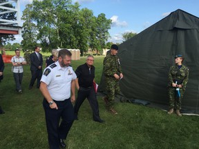 Public Safety Minister Ralph Goodale, in black, tours the tent city constructed outside the Nav Centre in Cornwall, Ont., after meeting with the city council to discuss their concerns about how the operation to house asylum seekers is being run. (Handout/Cornwall Standard-Freeholder/Postmedia Network)