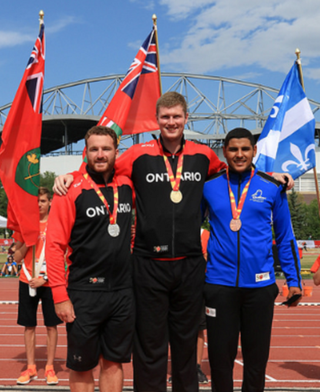 Clinton's Mackenzie Josie (centre) poses with his competitors and the gold medal he won for his 50.38 m discus throw at the Canada Summer Games earlier this month.