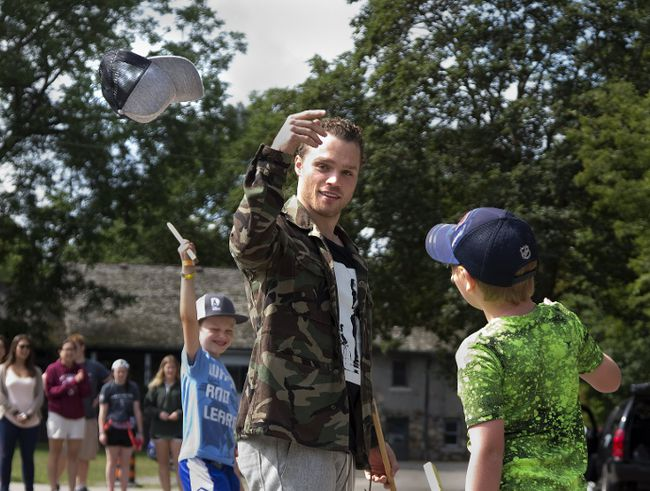 Max Domi tosses his cap after Mikey Polci, 11, right, scored a hat trick during a road hockey game at Camp Discovery, a summer camp for children with diabetes in London.  Domi, an Arizona Coyote and former London Knight who suffers from diabetes himself, surprised campers with an unannounced visit.  (DEREK RUTTAN, The London Free Press)