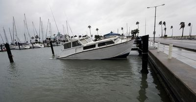 A fishing boat is left partial submerged after Hurricane Harvey swept through the area, Saturday, Aug. 26, 2017, in Corpus Christi, Texas. (AP Photo/Eric Gay)