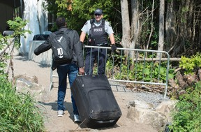 An asylum seeker, claiming to be from Eritrea, is confronted by an RCMP officer as he crosses the border into Canada from the United States on Aug. 21, 2017 near Champlain, N.Y. (Paul Chiasson/The Canadian Press)