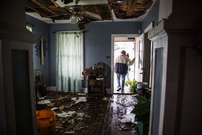 Lucas Garcia walks out of his home in Refugio, Texas on Aug. 26, 2017. Garcia and other family members rode out Hurricane Harvey in a single room in their home (Olivia Vanni/The Victoria Advocate via AP)