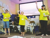 Bible School leader Verna Powley (l.) and her two assistants lead participants in an action song during Vacation Bible School.