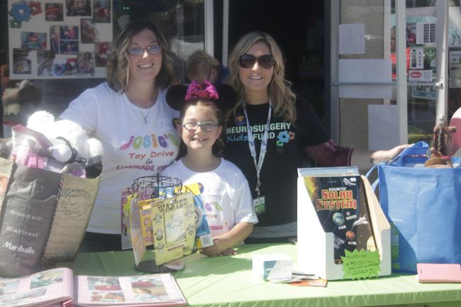 From the left, Jen MacKinnon, Josie MacKinnon and Soula Milonas stand together at the toy drive on Aug. 25 (Joseph Quigley | Whitecourt Star).
