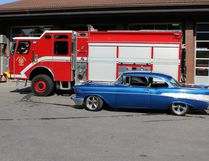 Allan Russell sits aboard Canmore's newly custom-designed Emergency Response vehicle while RSCC member Steve Hall's 1957 Chevy Bell air is parked alongside.