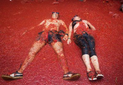 """Revellers covered in tomato pulp take part in the annual """"Tomatina"""" festival in the eastern town of Bunol, on August 30, 2017. JAIME REINA/AFP/Getty Images"""