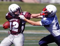Bantam Lions running back Shawn Clazie straight-arms a Cowboy Navy player as the opponent face-masks Clazie which escaped the referee's flag during the Lions first game of the year which they lost 34-13, August 26.