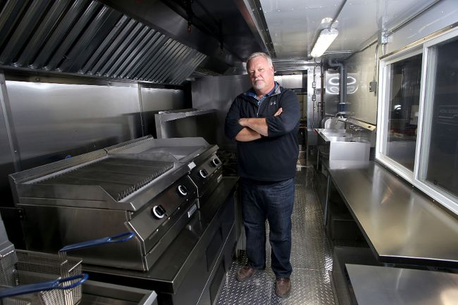 David Craig with a large mobile kitchen truck in his garage at Mobile Kitchens Canada north of Kingston.