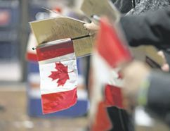 A new citizen holds a Canadian flag during a citizenship ceremony held in Edmonton. A 2014 government report, recently released, outlines areas where Canadian immigrants have increasing struggles. (Postmedia file photo)