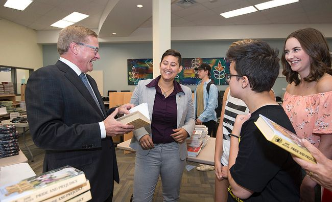 Education Minister David Eggen (left) and Strathcona MLA Estefania Cortes-Vargas (centre) laugh with students while visiting Archbishop Jordan Catholic High School for an announcement in school fee reduction throughout the province.