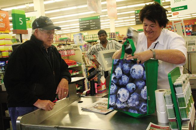 Sterling Lingan, left, receives his first free reusable bag at the downtown Sobey's in Fort McMurray, Alta. on Sept. 1, 2010. Shirley Lin/Fort McMurray Today