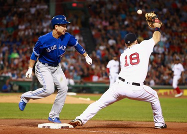 Darwin Barney #18 of the Toronto Blue Jays safe at first base after a throwing error by short stop Xander Bogaerts #2 of the Boston Red Sox as Mitch Moreland #18 reaches for the ball in the top of the fourth inning during the game at Fenway Park on September 5, 2017 in Boston, Massachusetts.  (Photo by Omar Rawlings/Getty Images)