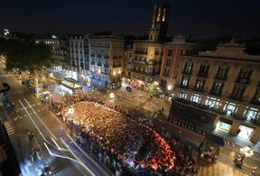 A general view taken on the Rambla boulevard in Barcelona on August 26, 2017 shows people gathering around a flower tibute for the victims of last week's deadly attacks during a march against terrorism which slogan is #NoTincPor (I'm Not Afraid). Tens of thousands of Spaniards and foreigners stagged a defiant march against terror through Barcelona following last week's deadly vehicle rampages. The Mediterranean city is in mourning after a van ploughed into crowds on Las Ramblas boulevard on August 17, followed hours later by a car attack in the seaside town of Cambrils. / AFP PHOTO / LLUIS GENELLUIS GENE/AFP/Getty Images