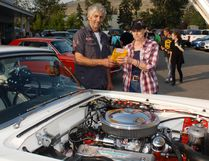 Derald Anderson of the Cochrane Classic Car Club gives Vivian Smith an envelope containing close to $300 that the members collected for her daughter Vicki Smith, who is stricken with breast cancer, during one of the club's car shows.