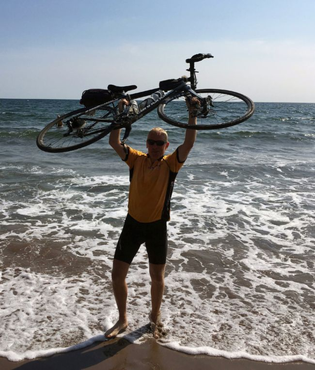 Simcoe's Ted Berkel raises his bike in celebration at the completion of the Sea to Sea bicycle mission. The ten-week journey saw Berkel and 49 others complete a 4,200 mile ride from Vancouver to Halifax in support of ending poverty. Contributed Photo