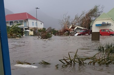 """TOPSHOT - This handout picture released on September 6, 2017, on the twitter account of RCI.fm shows a flooded street on the French overseas island of Saint-Martin, after high winds from Hurricane Irma hit the island.  Monster Hurricane Irma slammed into Caribbean islands today after making landfall in Barbuda, packing ferocious winds and causing major flooding in low-lying areas. As the rare Category Five storm barreled its way across the Caribbean, it brought gusting winds of up to 185 miles per hour (294 kilometers per hour), weather experts said. / AFP PHOTO / TWITTER AND rci.fm / Rinsy XIENG / RESTRICTED TO EDITORIAL USE - MANDATORY CREDIT """"AFP PHOTO / RCI.fm/ Rinsy XIENG"""" - NO MARKETING NO ADVERTISING CAMPAIGNS - DISTRIBUTED AS A SERVICE TO CLIENTS --RINSY XIENG/AFP/Getty Images"""