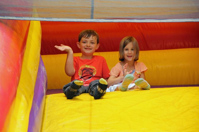 Daniel Mclaughlin and Vienna Kerr wave to their teachers and classmates before zipping down the inflatable slide.