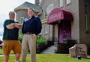 Sam Shoebottom, left, and John Allen stand in front of the historic Princess Avenue Playhouse, a church converted to a stage for the Elgin Theatre Guild in 1987. The production company turns 50 this year, and showrunners are looking for ways to keep it alive at a time when most entertainment has gone digital. (Louis Pin/The Times-Journal)