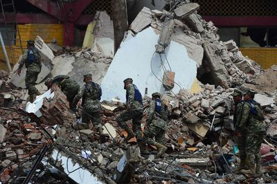 Mexican Navy members walk amid debris of the Town Hall building which partially collapsed following a massive earthquake that hit Mexico's Pacific coast, in Juchitan de Zaragoza, state of Oaxaca on Sept. 8, 2017. (RONALDO SCHEMIDT/AFP/Getty Images)