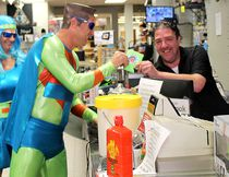 Craig Francis, of Chatham-Kent Pawn Brokers, gets some swag from Capt. Positive and OptiWoman during Support Your Local Business Day, held in Chatham, Ont. on Saturday September 9, 2017. Ellwood Shreve/Chatham Daily News/Postmedia Network