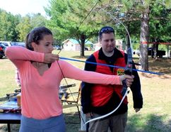 Sean Chase/Daily Observer Pembroke Outdoor Sportsman's Club hosted its annual open house last Saturday. Here volunteer Mark Solimine coaches new member Tuesdae Doyle on how to aim and shoot a bow-and-arrow. The club has promoted hunting, fishing and conservation in the area since 1958.