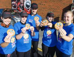 Tim Hortons staff at the Arlington Park Place location, along with Maclaine Chadwick from the University Hospitals Kingston Foundation, far right, stand outside the store on Saturday showing off a batch of practice Smile cookies they've been working on in preparation for the $1 Smile Cookie campaign, Sept. 11-17. (Julia McKay/The Whig-Standard)