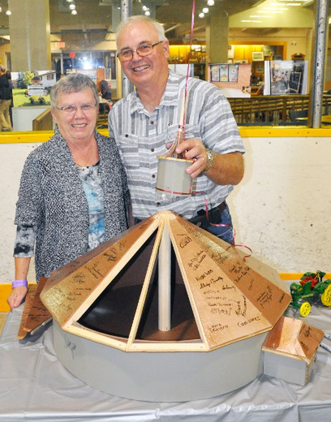 Winston and Sheila Jibb pose with the scale model Winston built of the Crystal Palace they had on display during the 163rd Mitchell & District Agricultural Society's fall fair Sept. 1-3. The Crystal Palace was marking its 100th birthday and the Jibbs, who were longtime caretakers of the building even when they lived just outside of Mitchell on their farm, thought it be a great idea for the public to sign the model and have it on display in the future. Ironically enough, the Crystal Palace marked exactly 100 years of being opened Sept. 1, having been officially opened on Sept. 1, 1917 after it burned to the ground one year earlier. ANDY BADER/MITCHELL ADVOCATE