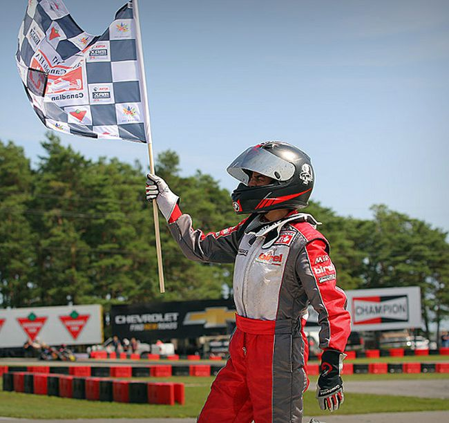 Junior Lindgren waves the checkered flag after winning the Briggs Junior national title in Bowmanville on Aug. 27. Canadian Karting news photo