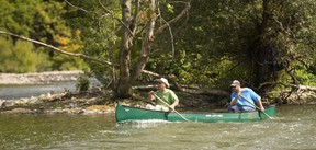 John Hlodan, left, and son Ryan paddle the Thames River just below the broken Springbank Dam Monday. A local angler?s recent catch of a muskie in the river has renewed questions about the value or repairing the dam. (MIKE HENSEN, The London Free Press)