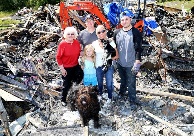 Dan and Leeanne Smith are seen with their daughter Emma, 8, son Josh, 19, Leeanne's mother, Pheme Bennett, and the two dogs that survived the fire, Darby, lower left, and Morgan. (Ian MacAlpine/The Whig-Standard)