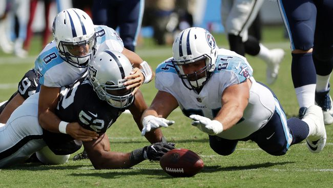 Tennessee Titans offensive guard Josh Kline recovers a fumble by quarterback Marcus Mariota as Oakland Raiders defensive end Khalil Mack also scrambles for the ball in the second half of an NFL game on Sept. 10, 2017. (AP Photo/James Kenney)