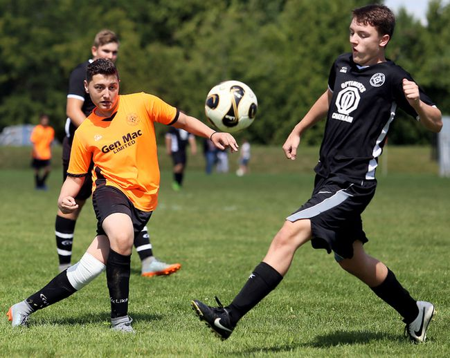 Gen Mac's Alexander Pelekis, left, kicks the ball away Optimist Club's Alex Bugajski during the Chatham Youth Soccer Association under-17 boys' final at the Keil Drive soccer complex on Saturday, Sept. 9, 2017. (MARK MALONE/The Daily News)
