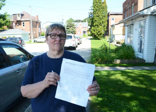 Monika Brauer with a petition calling for something to be done to clean up her neighbourhood. (Rob Gowan The Sun Times)