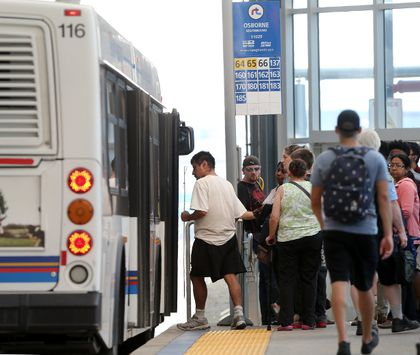 Transit users board a bus.