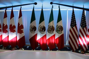 National flags representing Canada, Mexico, and the U.S. are lit by stage lights at the North American Free Trade Agreement, NAFTA, renegotiations, in Mexico City, Tuesday, Sept. 5, 2017. THE CANADIAN PRESS/AP/Marco Ugarte
