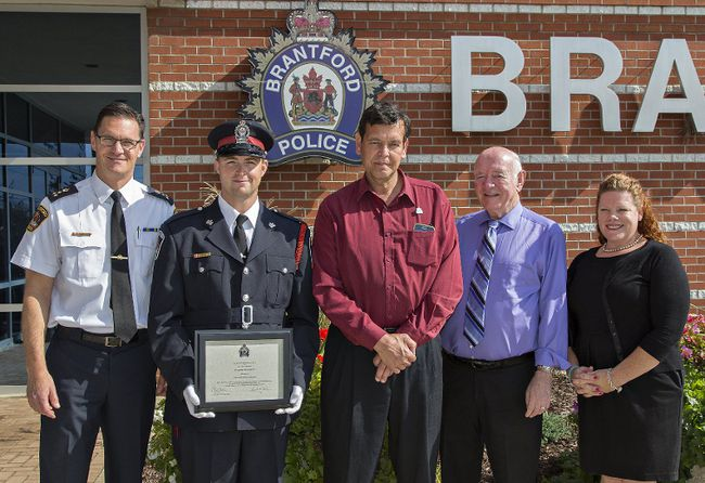 Brantford Police Chief Geoff Nelson (left) stands with Const. Jeremy Morton and retired auxiliary staff sergeant Norm Barrieau, who were honoured on Thursday by the Brantford police services board, including Brendan Ryan and chair Deb Cockerill. (Brian Thompson/The Expositor)