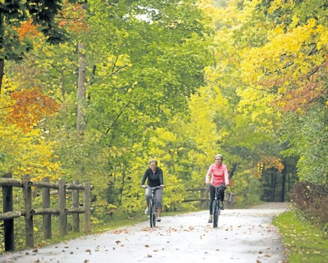 Wilma Dykstra and Mary-Anne Cross of St. Thomas ride through the fall colours along the Thames River in London. (MIKE HENSEN, The London Free Press file photo)