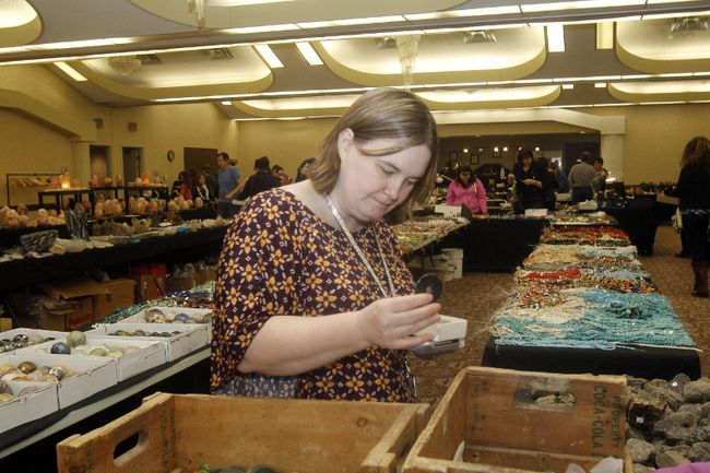 Melissa Robak, co-owner of Silver Cove, a rock and gem store based in Lacombe, examines a piece of granite for a customer at the Grande Prairie Gem and Mineral Show at the Paradise Inn and Conference Centre on 100 Avenue on Wednesday April 8, 2015 in Grande Prairie, Alta.(Postmedia File Photo)