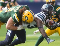 Argonauts running back James Wilder Jr., gets tackled by Alex Hoffman-Ellis of the Eskimos in the first half of yesterday's tilt. (The Canadian Press)