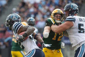 Argonauts running back James Wilder Jr. (left) finds space in the Eskimos defence on Saturday. (Chris Young/The Canadian Press)