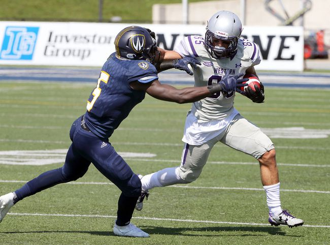 Western Mustangs receiver Malik Bessehieur, right, uses a stiff arm against Windsor Lancers Lekan Idowu in OUA action from University of Windsor Alumni Field September 16, 2017. (NICK BRANCACCIO/Windsor Star)