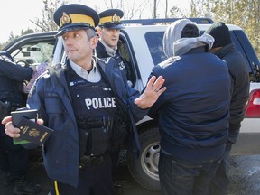 RCMP officers detain a group of asylum seekers who crossed from the U.S. into Canada illegally at the border at Roxham Road in Hemmigford south of Montreal, Monday February 20, 2017. (Phil Carpenter/MONTREAL GAZETTE)