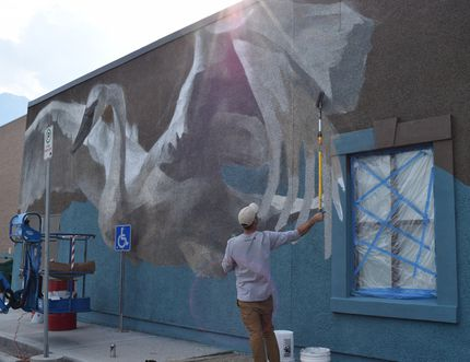 Artist Jarus works on a mural on artsPlace in Canmore as part of the Canada 150 mural project. Jarus is also the artist for the Lake Louise and Exshaw murals.