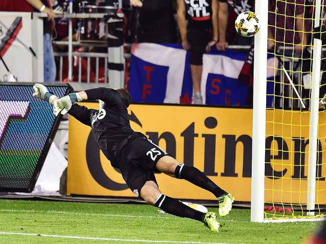 Toronto FC goalkeeper Alex Bono lets in a goal by Montreal's Marco Donadel during Wednesday night's game. (THE CANADIAN PRESS)
