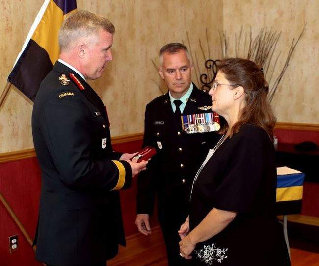 DND Photo Brig.-Gen. Stephen Cadden, commander of 4th Canadian Division (left) presents Anita Cenerini, mother of Private Thomas Welch, with the Sacrifice Medal. Looking on is 4th Canadian Division sergeant-major Chief Warrant Officer Stuart Hartnell.