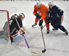 Edmonton Oilers Ben Betker (76) and Jussi Jokinen (36) fight for the puck in front of goalie Nick Ellis during the first day of training camp at Rogers Place in Edmonton, September 15, 2017.