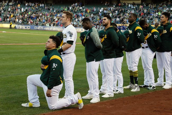 Oakland Athletics catcher Bruce Maxwell kneels during the U.S. National Anthem before the start of a baseball game against the Texas Rangers Saturday, Sept. 23, 2017, in Oakland, Calif. Bruce Maxwell of the Oakland Athletics has become the first major league baseball player to kneel during the national anthem. (AP Photo/Eric Risberg)