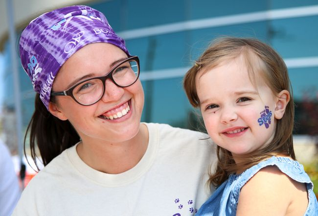 Tim Miller/The Intelligencer Kaitlyn Bell sits with her niece, Holly Dowling, at the face-painting booth at the 8th Annual Sarcoma Step and Fetch on Sunday in Trenton. The event was originally created by Teresa Bell, Kaitlyn and Holly's mother and grandmother (respectively). Teresa Bell died in December of last year and organizers say Saturday's event was about celebrating her life.