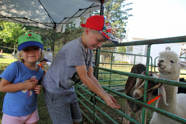 Siblings Margaret and Frederich Zadow (left to right) made some new friends at the K&M Hobby Farm petting zoo that dropped by the Champlain Trail Museum and Pioneer Village for the pop-up Canadiana event on Saturday.